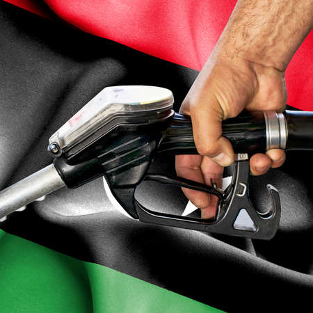 Gasoline consumption concept - Hand holding hose against flag of Libya Foto de archivo