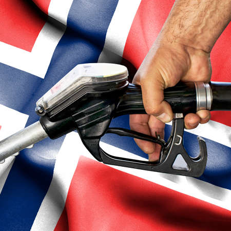 Gasoline consumption concept - Hand holding hose against flag of Norway