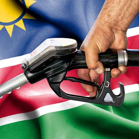 Gasoline consumption concept - Hand holding hose against flag of Namibia Foto de archivo