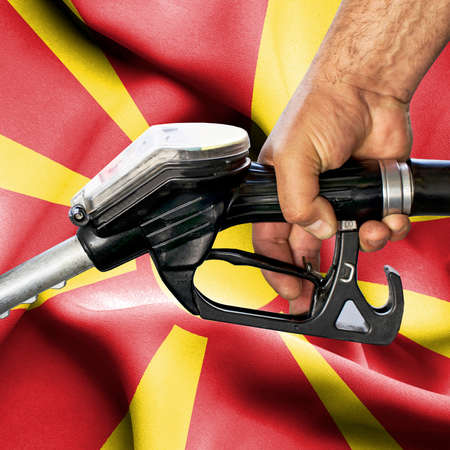 Gasoline consumption concept - Hand holding hose against flag of Macedonia Archivio Fotografico