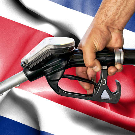 Gasoline consumption concept - Hand holding hose against flag of Costa Rica