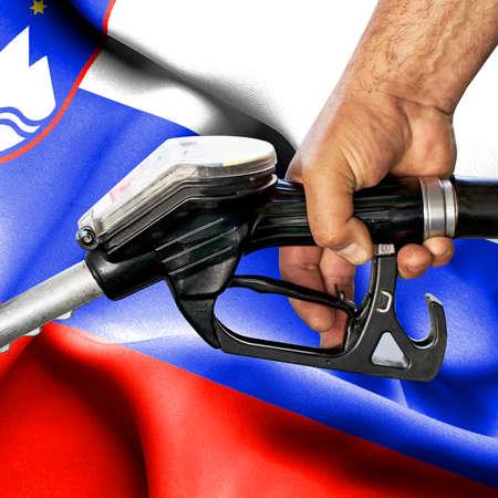 Gasoline consumption concept - Hand holding hose against flag of Slovenia