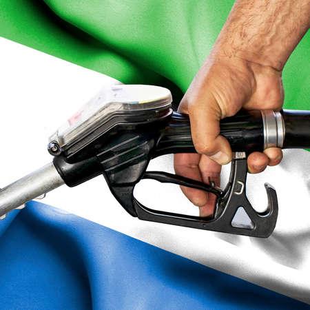 Gasoline consumption concept - Hand holding hose against flag of Sierra Leone Foto de archivo