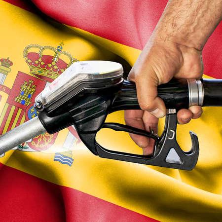 Gasoline consumption concept - Hand holding hose against flag of Spain