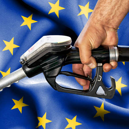 Gasoline consumption concept - Hand holding hose against flag of European Union