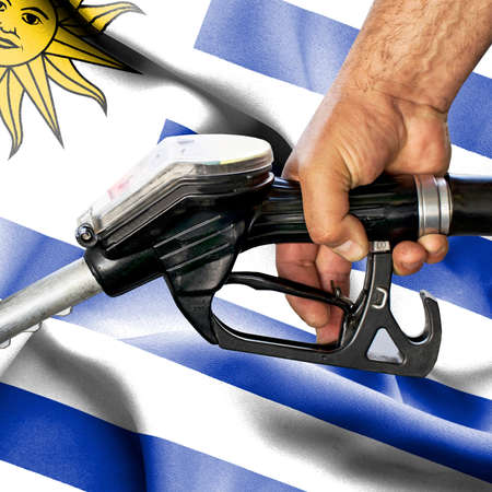 Gasoline consumption concept - Hand holding hose against flag of Uruguay Foto de archivo