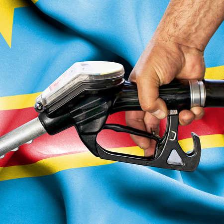 Gasoline consumption concept - Hand holding hose against flag of Congo Democratic Republic