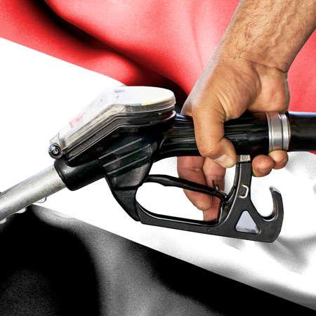 Gasoline consumption concept - Hand holding hose against flag of Yemen