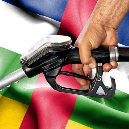 Gasoline consumption concept - Hand holding hose against flag of Central African Republic Foto de archivo