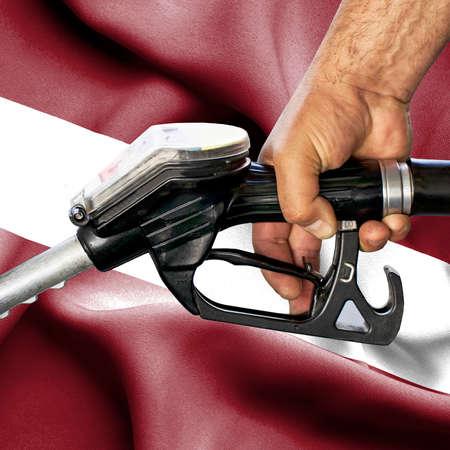 Gasoline consumption concept - Hand holding hose against flag of Latvia