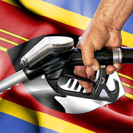 Gasoline consumption concept - Hand holding hose against flag of Swaziland Foto de archivo