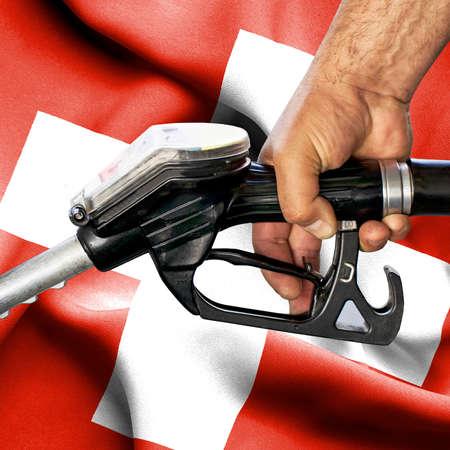 Gasoline consumption concept - Hand holding hose against flag of Switzerland