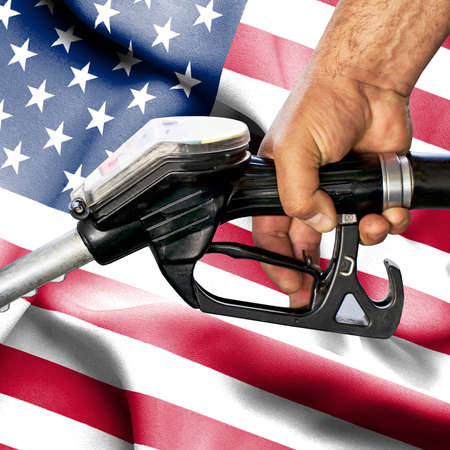 Gasoline consumption concept - Hand holding hose against flag of United States of America Foto de archivo