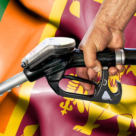 Gasoline consumption concept - Hand holding hose against flag of Sri Lanka