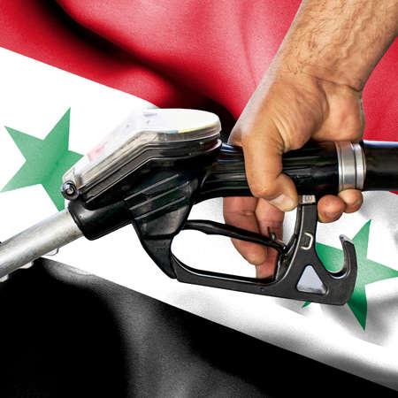 Gasoline consumption concept - Hand holding hose against flag of Syria