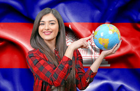 Young female Tourist holding Earth Globe against flag of Cambodia