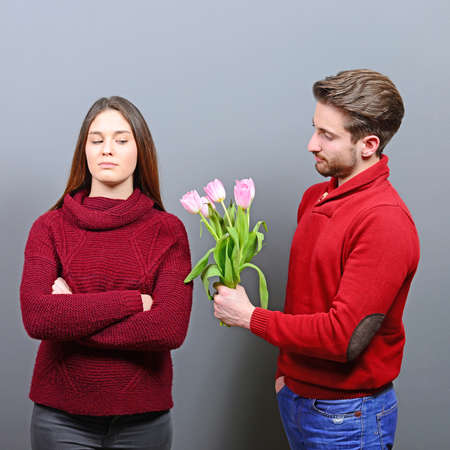 Portrait of unhappy young woman getting flowers from man she doesnt like or feels uncomfortable