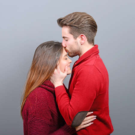Young man kisses a woman in the forehead