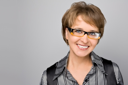 Portrait of the business woman in glasses on a grey background photo