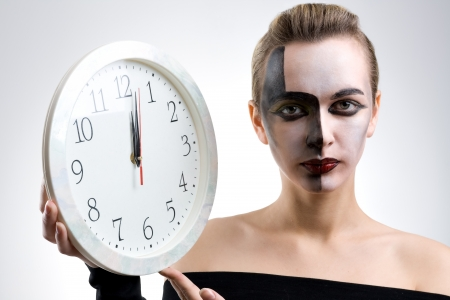 bodyart: Young and beautiful woman holding a clock