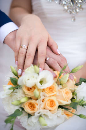 Hands and rings of the bride and groom on wedding bouquet