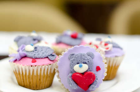 Cupcakes with teddy bear and hearts on white rustic background. Valentines Day cupcake.