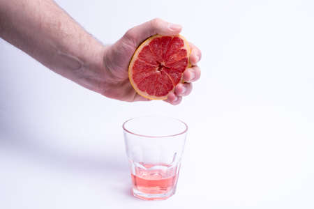 Male hand gripping a grapefruit, grapefruit juice on white background Stock Photo