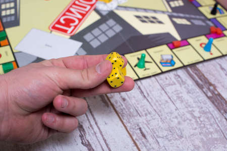 Hand throws the dice on the background of colorful blurred fantasy Board games, gaming moments in dynamics Stock Photo