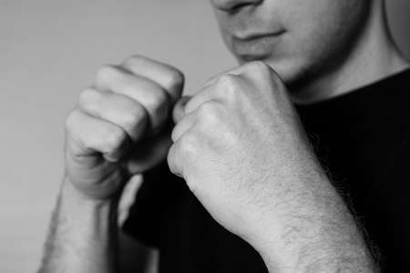 clenching: Close-up portrait of a young man standing in boxer position and ready to fight clenching his fists, in black t-shirt Stock Photo