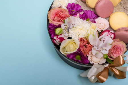 Box with flowers and macaroons on blue background, top view, with space for text