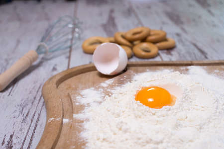 Baking concept. Sprinkled flour and eggs on wooden cutting board, cooking ingredients. Prepare for making yeast dough. Top view, copy space Stock Photo