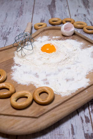pin board: Baking concept. Sprinkled flour and eggs on wooden cutting board, cooking ingredients. Prepare for making yeast dough. Top view, copy space Stock Photo