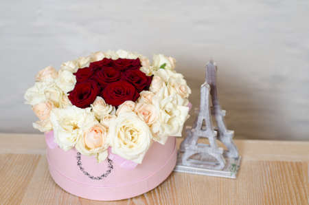 gift pink box with beautiful bouquet of blooming red and white roses standing on the wooden table. Symbol of romantic moment and Valentines Day.