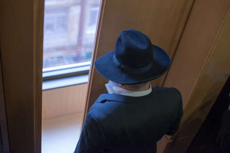 jewish: Jew Hasid ethnic headdress. The Jew prays before the window. view from above Stock Photo