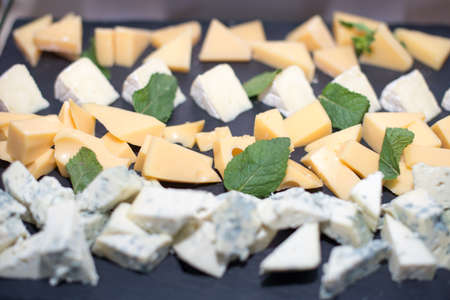 Different types of cheeses on black board. Selective focus.yield