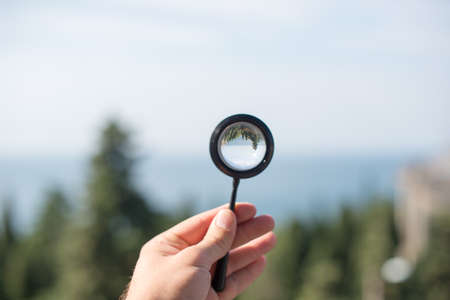 Man hand, magnifying glass in focus, nature, sea, trees on background.