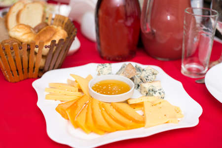 Cheese plate with honey, Dor Blue, Parmesan, Bree, Camembert and Roquefort in a table setting with a red tablecloth