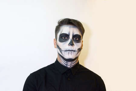 man in make-up Halloween. drawing a vampire, skeleton on his face. Close-up photo. 免版税图像