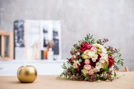 beautiful modern wedding bouquet on the table. Against the gray wall