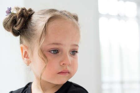 Beautiful sad little girl crying, on background white window. Stockfoto