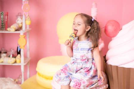 beautiful cute little girl eating lollipop. Interior macaroons, cake, muffin, cake sweets