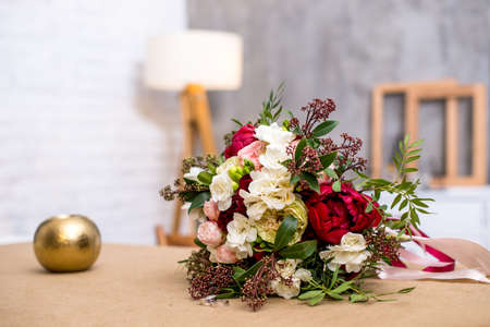 beautiful modern wedding bouquet on the table. with wedding rings near the bouquet. Against the gray wall. beautiful interior Stock Photo