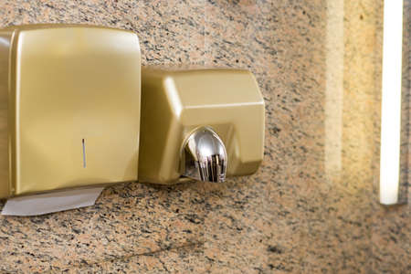 Paper Dispenser and hand dryer on the wall in public toilet