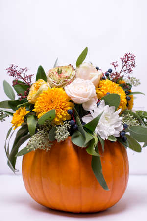 Autumn floral bouquet in a pumpkin vase on a light background, a mixture of flowers, pionic rose, eucalyptus, chrysanthemum.