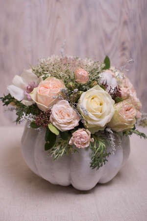floral bouquet in a white pumpkin on a light background, a mixture of flowers, peony rose, eucalyptus, chrysanthemum, Brassica, white orchid, cotton.