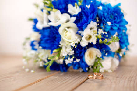 Beautiful modern wedding bouquet of blue chrysanthemum, freesia, roses and peony. on wooden background. With rings newlyweds.