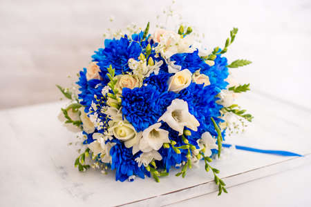 Beautiful modern wedding bouquet of blue chrysanthemum, freesia, roses and peony. on white wooden background.