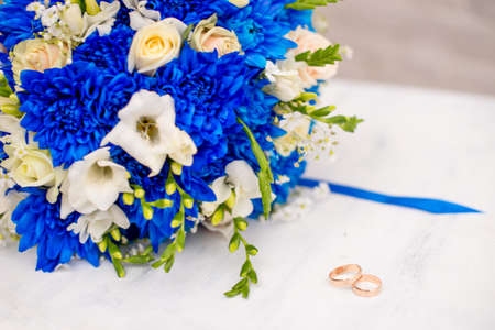 Beautiful modern wedding bouquet of blue chrysanthemum, freesia, roses and peony. on white wooden background. With rings newlyweds. Stock Photo