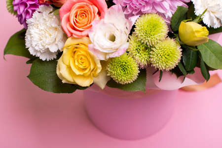 beautiful floral arrangement in the box, pink and yellow rose, pink eustoma, green and pink chrysanthemum, white carnation, pink dahlia on pink background with space for text.
