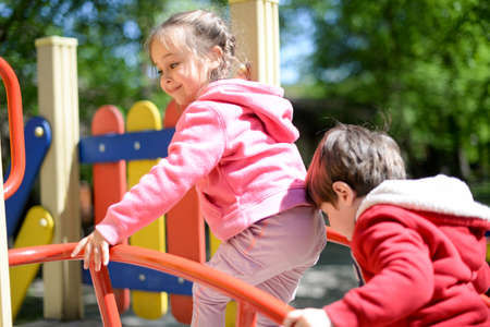 Two happy children playing on the playground at the day time. Concept brother and sister forever Stockfoto